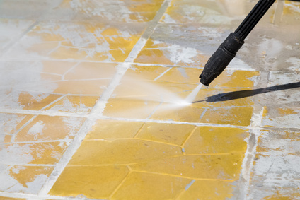 Close-up of a pressure washer being used to clean an outdoor floor.